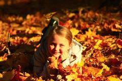 Little girl laying in yellow leaves Stock Photos