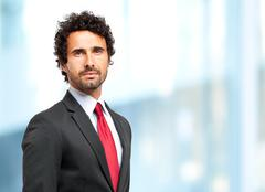 Handsome businessman against blurry background - stock photo