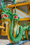 Green naka statue in front of Thai Buddhist pagoda at Tiger Cave Temple , Kra - stock photo