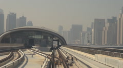 POV Point of view Dubai metro train enter station modern district skyscraper day Stock Footage