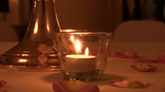 Candelabra , candles and rose petals on the table in a restaurant . Night time. - stock footage