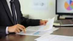 Businessman analyzing financial statistics  Stock Footage
