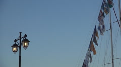 A lamp lit in a Mediterranean harbor, in dusk, near some flags of anchored boat. Stock Footage