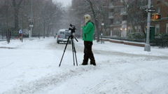 Filmmaker tripod street video taping blizzard 4k slow motion snowing NYC Stock Footage