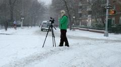 filmmaker tripod street video taping blizzard 4k slow motion snowing NYC - stock footage
