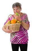 Senior woman biting into an apple - stock photo