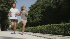 Sport couple running jogging in city park - Runners exercising - stock footage