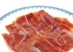 Closeup of serrano ham slices on a dish. Jabugo. Spanish tapa Stock Photos