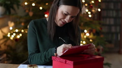 Happy woman in the room writing a christmas cards HD Stock Footage