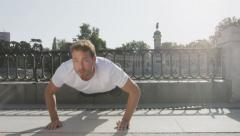 Athlete doing push-ups on run in park - Fitness guy exercising Stock Footage