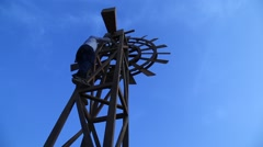 Close-up to a rotating windmill for pumping water over blue sky - stock footage