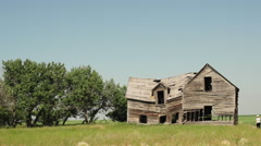 Photographer takes pictures of a dilapidated farm house in a field Stock Footage