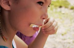 Girl eating ice lolly - stock photo