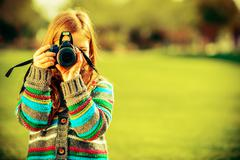 Caucasian Girl with Large Modern DSLR Camera Taking Pictures in Park. - stock photo