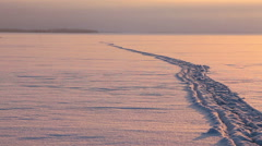 Pathway to the horizon on the snowy ice of winter lake with strong sundown - stock footage