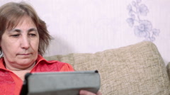 Elder woman looking at pad screen while using electronic device, close-up view - stock footage