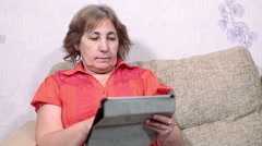 Adult woman sitting on couch and browsing with tablet pc. Domestic room Stock Footage