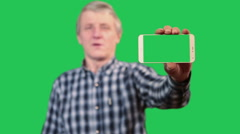 Mature man showing  cellphone with green screen, dialing number and calling Stock Footage