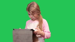 Girl having fun with tablet pc, turning with pad in all sides. Green chromakey  Stock Footage
