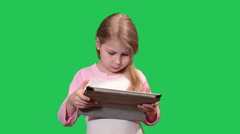 Pretty girl playing with tablet pc, bending in all directions. Green chromakey  Stock Footage