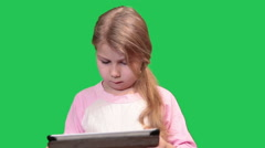 Pretty girl playing with tablet pc, turning all sides. Green chromakey backgrou Stock Footage