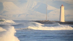 Heavy waves rolling by Grotta lighthouse, Reykjavik Iceland winter sunny day. - stock footage