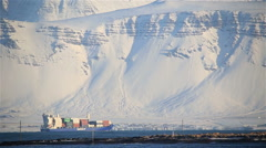 A fully loaded cargo ship sails by snowy mountains, Grotta lighthouse Iceland - stock footage