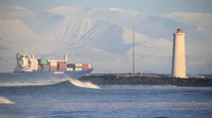 Fully loaded cargo ship sails by snowy mountains, Grotta lighthouse Iceland Stock Footage