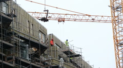 construction workers working on high rise building with crane, Reykjavik - stock footage