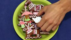 Hand takes gingerbread cookies of different shapes from a plate Stock Footage