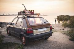 Old rusted hippie car freedom concept on coast Stock Photos
