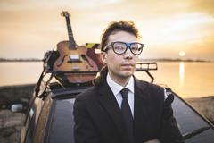 Hipter in glasses and his guitar on car rack - stock photo