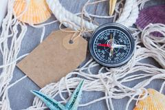 compass on fishing net with tag - stock photo