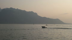 Boat on Geneva Lake. Sunset and mountains. Stock Footage