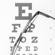 Eyesight test table with glasses over it Stock Photos