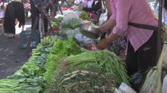 Lady Washing Vegetables in Asian Market [ProRes] Stock Footage