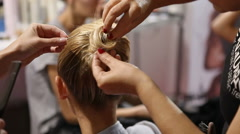 Hairdresser puts fashion model's hair in a bun Stock Footage
