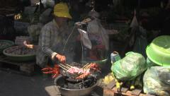 Lady Fanning Street BBQ in Busy Asian Market [ProRes] Stock Footage