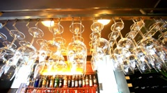 Empty glasses hanging at the bar and Bar with bottles Blurred Background. HD Stock Footage