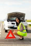 Woman placing emergency triangle - stock photo