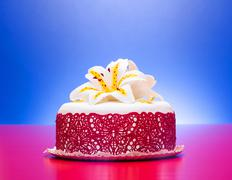 White fondant cake decorated with red lace and edible candy lily Stock Photos