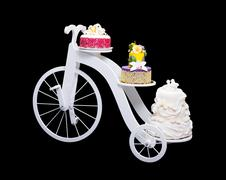 Unique bicycle cake stand with three cakes - stock photo