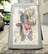 Street art bunny with a red dripping heart on the base of a sidewalk lamppost. Stock Photos