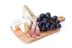 Blue cheese, camembert and dry sausage with grape Stock Photos