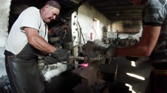 Blacksmith hammers beat on a hot metal piece on the anvil in an old smithy Stock Footage