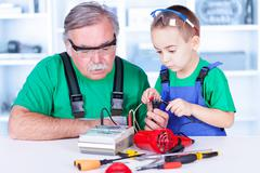 Grandfather and grandchild using multimeter Stock Photos