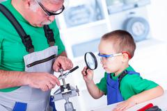Grandfather showing to grandchild the thread cutting die - stock photo