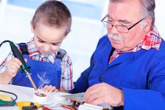 Grandfather teaching grandchild to use soldering resin - stock photo