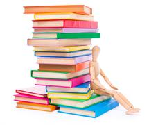 Wooden dummy puppet sitting on books Stock Photos