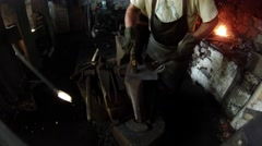 Blacksmith shoeing a shovel on the anvil Stock Footage
